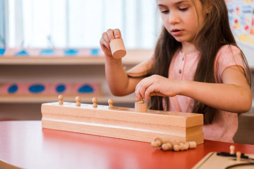 imagen de una niña usando cilindros de perilla montessori.