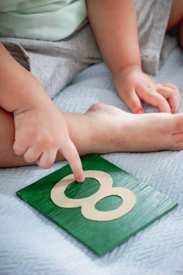 niño usando números de papel de lija montessori.