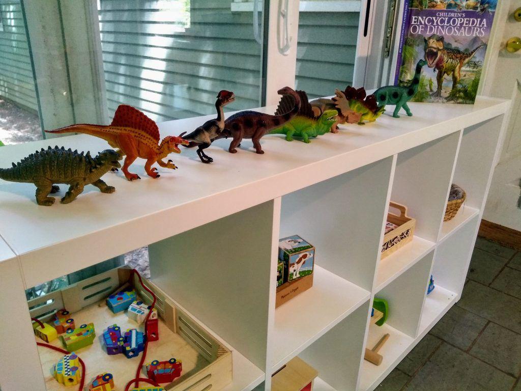 cómo organizar la imagen de la sala de juegos Montessori del estante lleno de regalos de madera y dinosaurios.