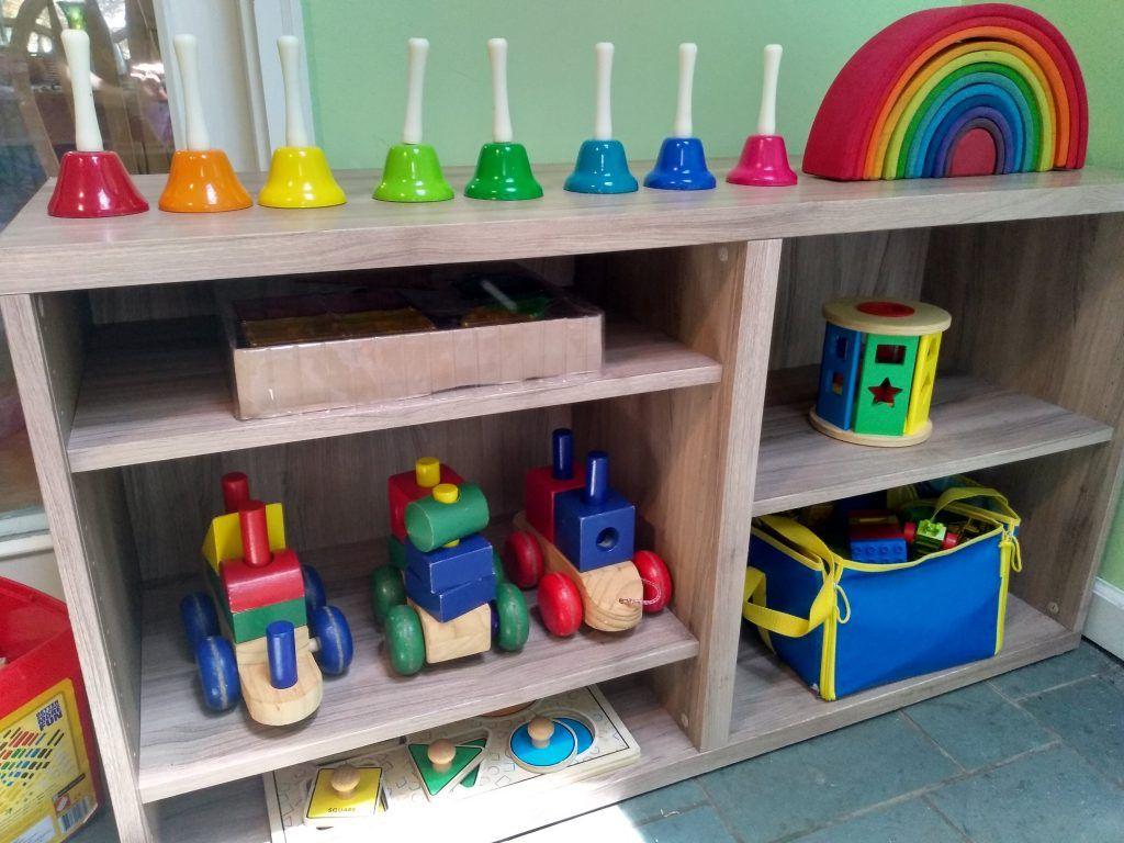 cómo organizar la sala de juegos: estantería con apilador arcoíris, rompecabezas, tren de madera, campanas sonando.